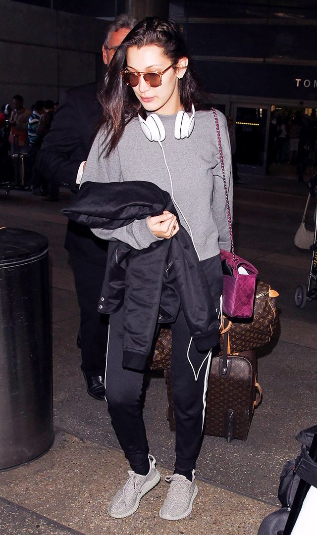 <p>Bella Hadid kept things sporty and wore a pair of Yeezy boosts with track pants, a comfy sweatshirt, and a bomber jacket.</p>