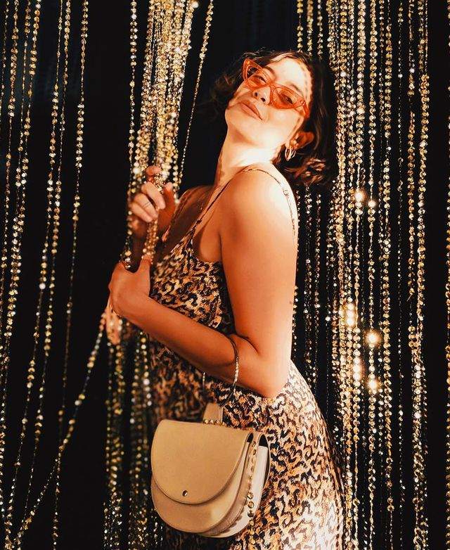 What to wear on a night out: Naomi Shimada wearing a leopard print dress and orange sunglasses