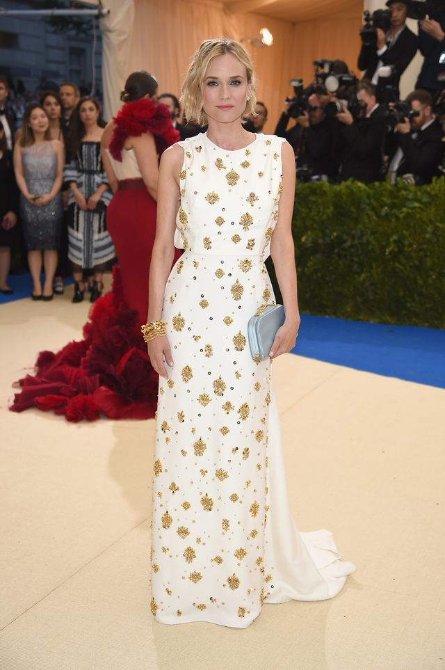<p><strong>WHO:</strong> Diane Kruger</p> <p><strong>WEAR:</strong> Prada white cady gown accented with asymmetric blouson bow back and train. Adorned at the front with clusters of gold and...
