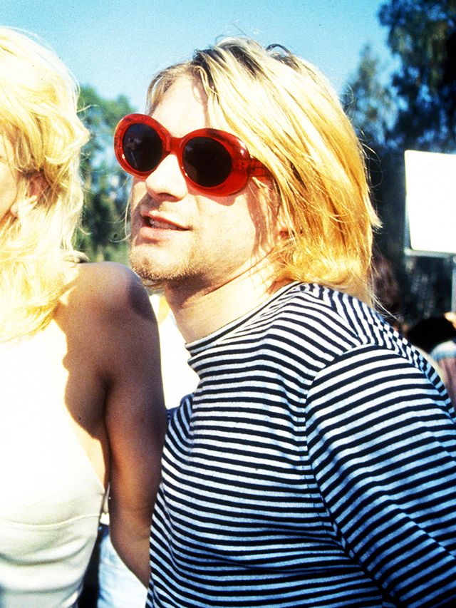 90s fashion: Kurt Cobain wearing red rounded oversized sunglasses