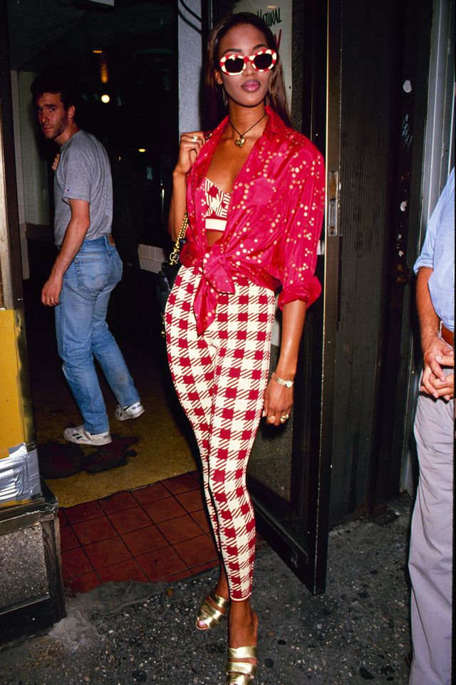 90s fashion: Naomi Campbell wearing red printed leggings with a tied shirt and bra top