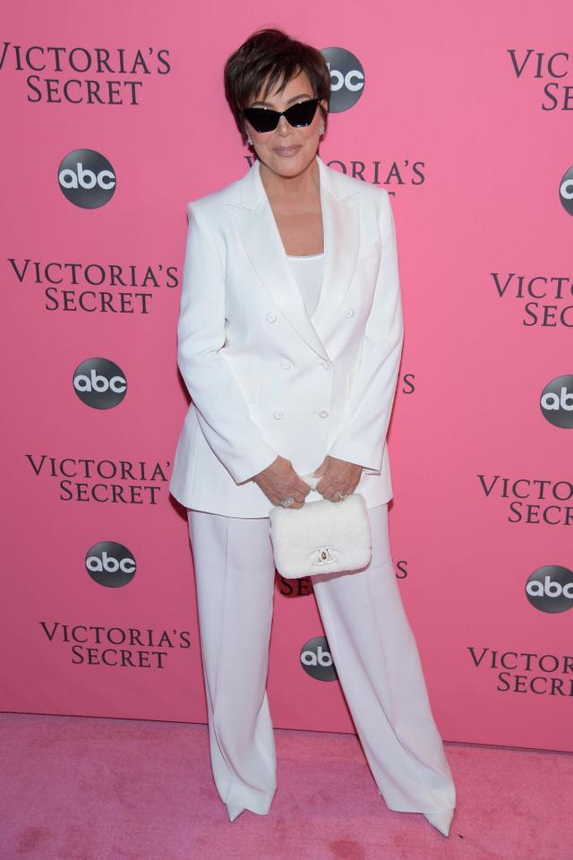 <p>Kris Jenner wearing a crisp white suit and faux fur mini bag.</p>