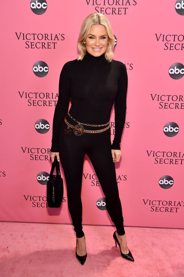 <p>Yolanda Hadid wearing a black catsuit with a gold chain belt and a black box bag.</p>