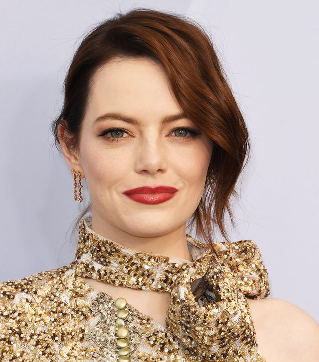 <p>It may be subtle, but if you look closely you'll see the rose gold shimmer of shadow beneath and atop Emma Stone's upper and lower lashlines. A complimentary shade of scarlet lipstick keeps the...