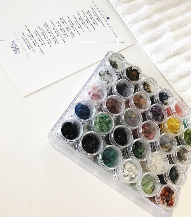 <p>Next, while Mazz cut, clipped, and buffed my nails to perfection, came the extra-fun part. She showed me the collection of crystals she keeps on hand for her manicures along with a menu listing...