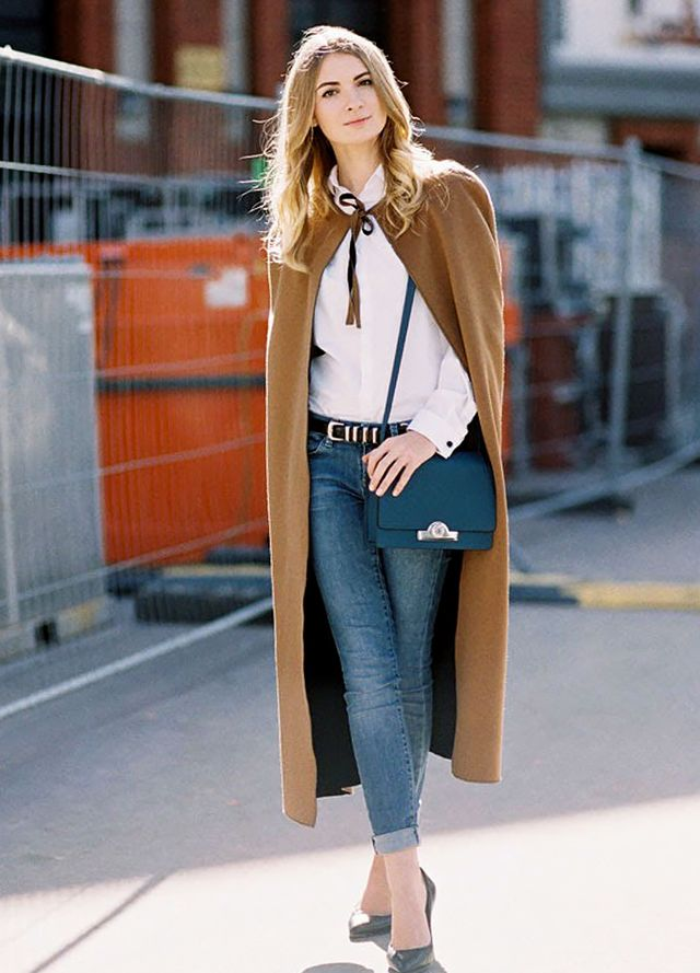 A camel cape adds a stylish touch to a casual outfit: