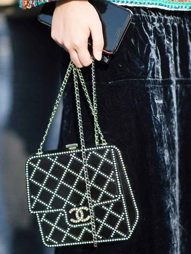How to Buy a Chanel Bag: fashion week street style shot of someone holding a Chanel bag