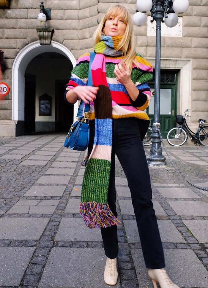 How to wear a scarf: Jeanette Madsen wearing a rainbow jumper with a striped scarf over one shoulder