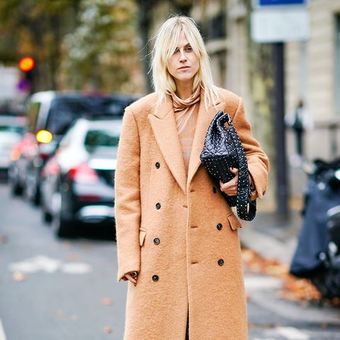 how to wear camel clothing: the top and the coat in camel with black jeans and black shoes