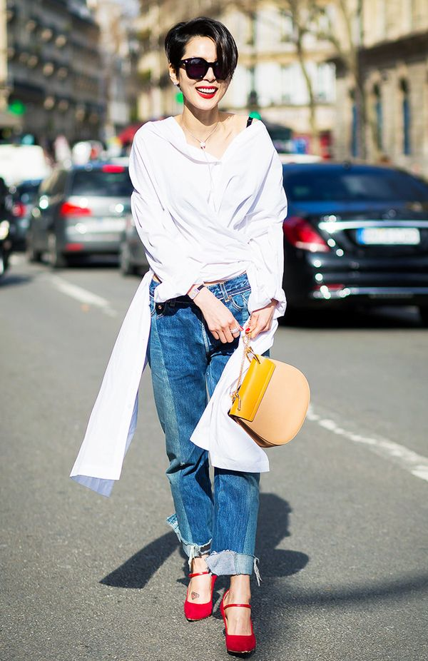 How to wear boyfriend jeans: street style star wearing a white shirt and red shoes with frayed boyfriend jeans