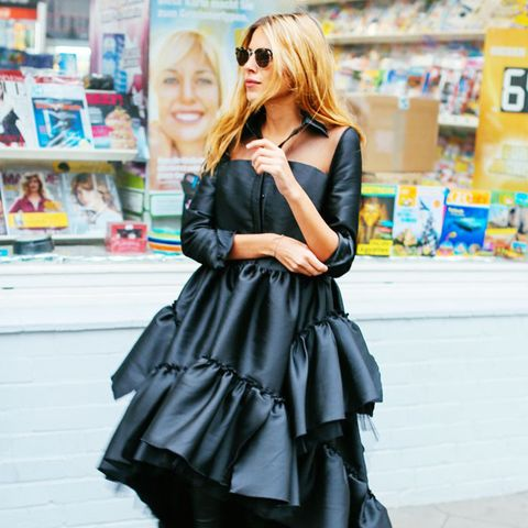 All-black outfits: Maja Wyh in a black dress over black jeans and boots