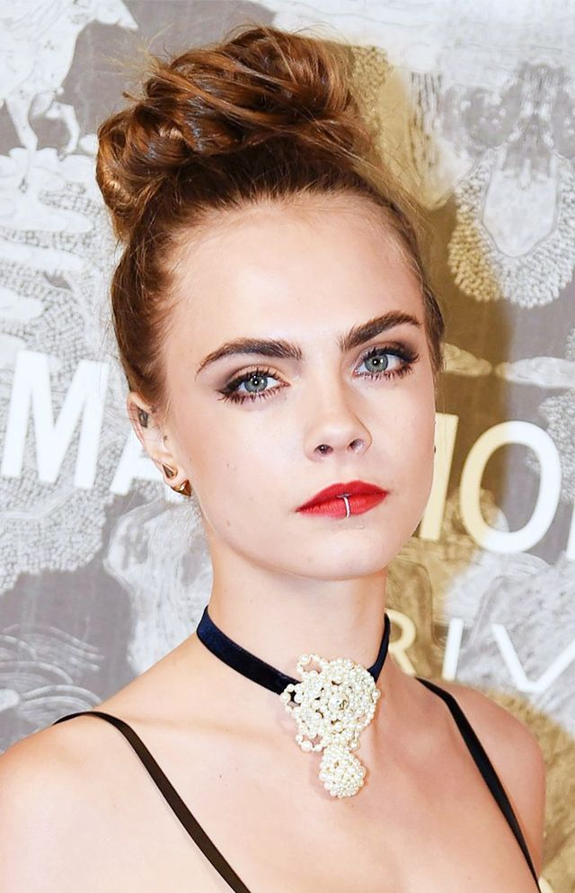 Cara Delevingne showed off her new lip ring, set against a slick of bold red lipstick.