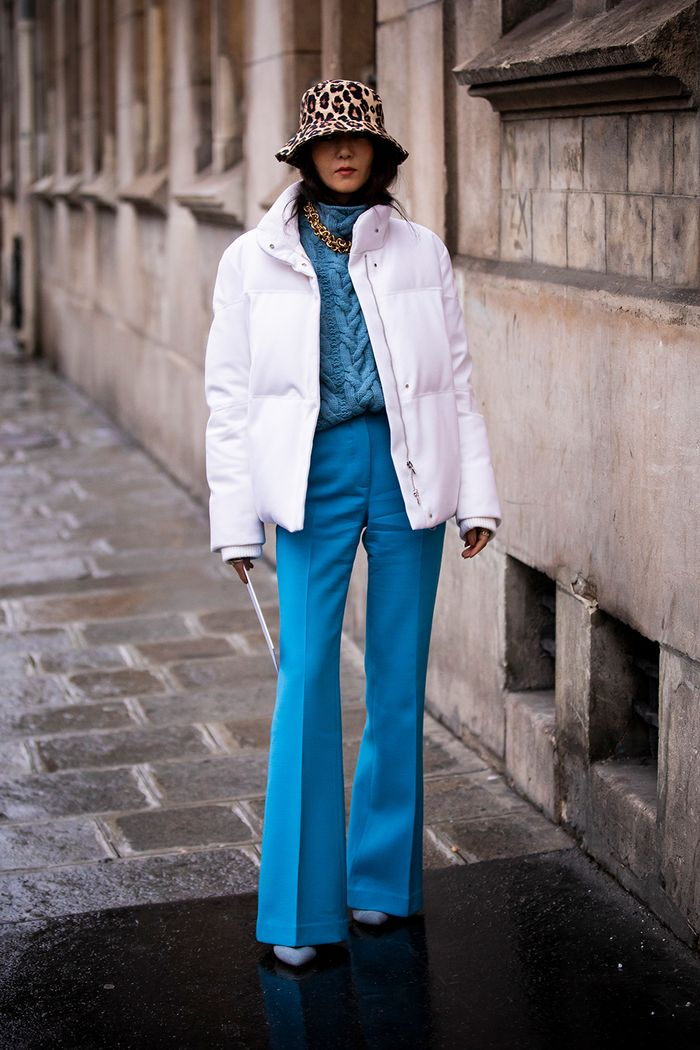 What to wear in cold weather: a white puffer with blue flares and a leopard bucket hat