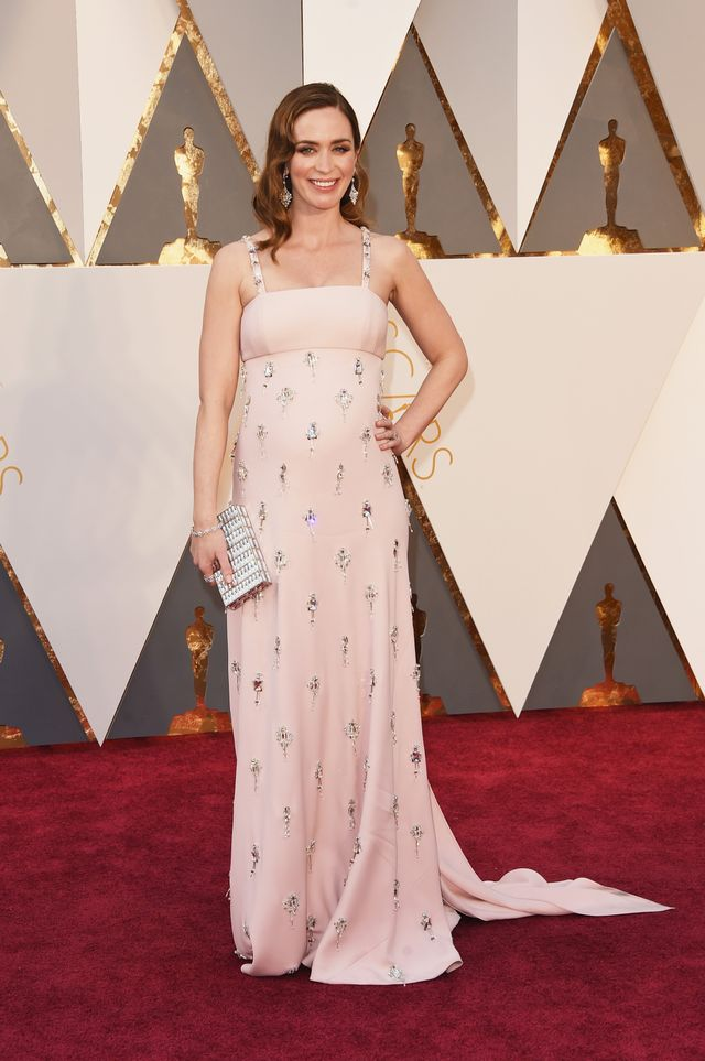 WHO:Emily Blunt WEAR: Prada blush pink cady empire waist gown enriched with crystal and damier embroidery; Sophia Webster shoes.
