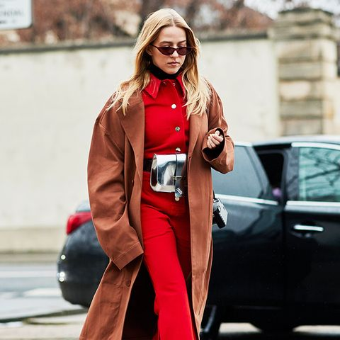 white shoes trend: street styler during paris fashion week wearing a red jumpsuit and white boots