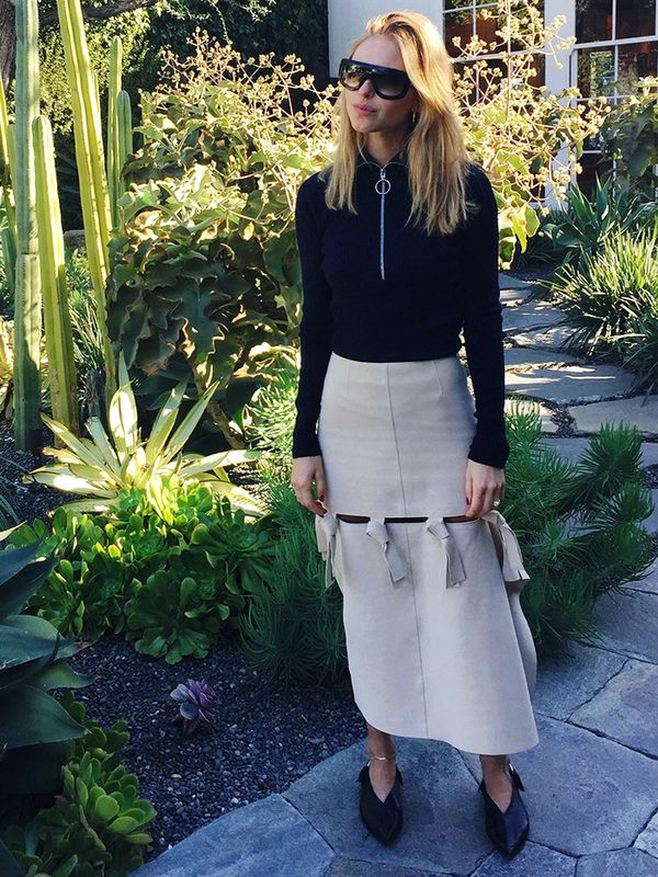 Style Notes: V-neck flats are also a clever way to make a midi more flattering. See how Pernille Teisbaek tops and tails her knotted statement skirt with long black lines?