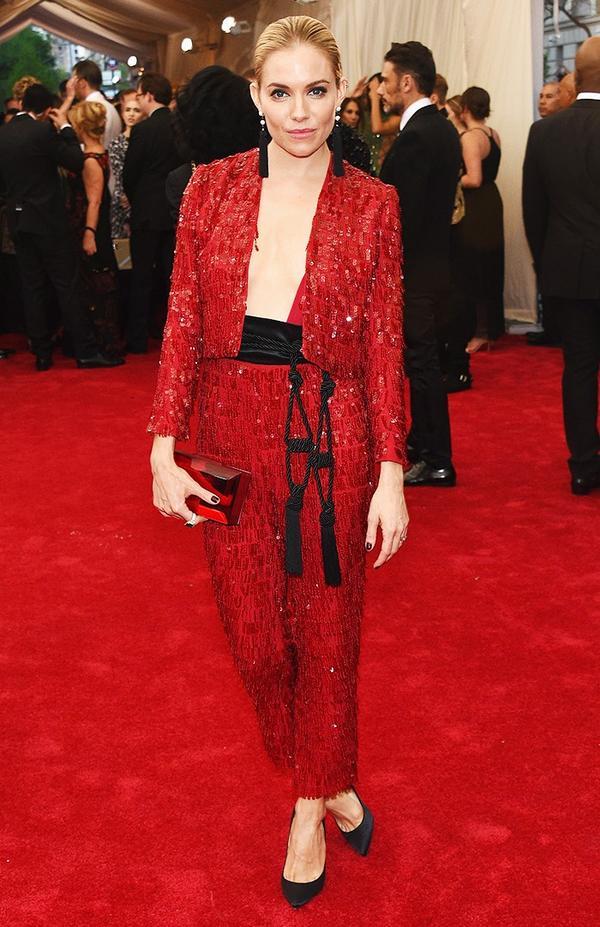 WHO:Sienna Miller WEAR:Thakoon red chiffon fringe sequined tuxedo with rope tassel belt; Jacob & Co. custom earrings.