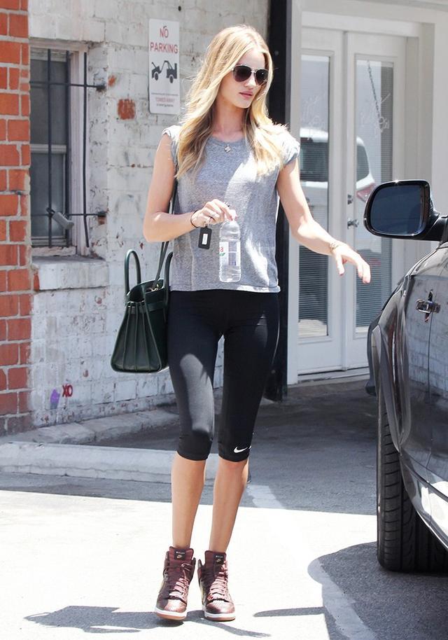 On Rosie Huntington-Whiteley: Nike capris; Saint Laurent Classic Small Sac du Jour Bag in Dark Green Grained Leather (£1890); Burberry sunglasses.