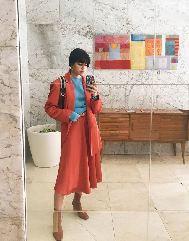 Spring street style outfit ideas 2018: red skirt suit styled with a blue sweater and tan boots