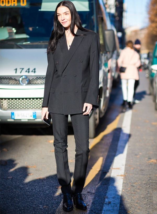 Style Notes: Mariacarla Boscono's sombre take on the trend (all black, flat shoes, wide shoulders) helps balance out the fact she's not wearing a top under that suit.