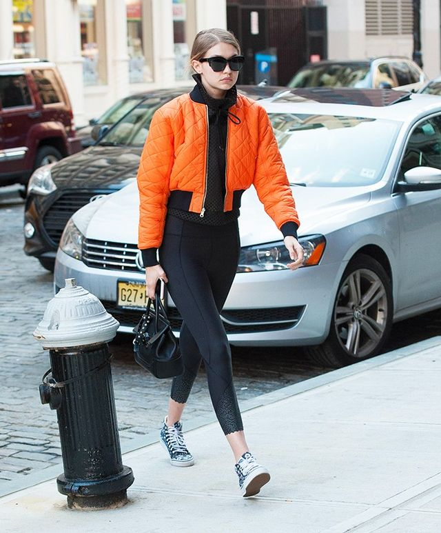 On Gigi Hadid: VFiles bomber; Koral pullover; Versace tote; Lululemon Tight Stuff Tight Leggings ($148); Vans Love Me, Love Me Not Sk8-Hi Slim Sneakers ($85).
