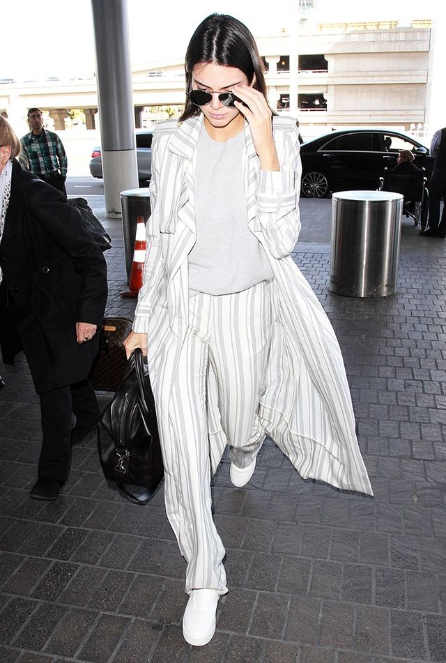 On Kendall Jenner: Ahlem sunglasses; Sally LaPointe Striped Silk Wood Duster Coat ($2250), Powder Blue Cashmere Tank ($1050), and pants.