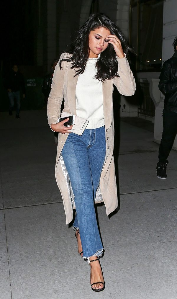 On Selena Gomez: Wes Gordon trench coat; CO Ruffled Merino Wool Sweater ($625); Vetements jeans; Louis Vuitton Iris Wallet ($1310); Jimmy Choo Minny Leather Sandals ($750).