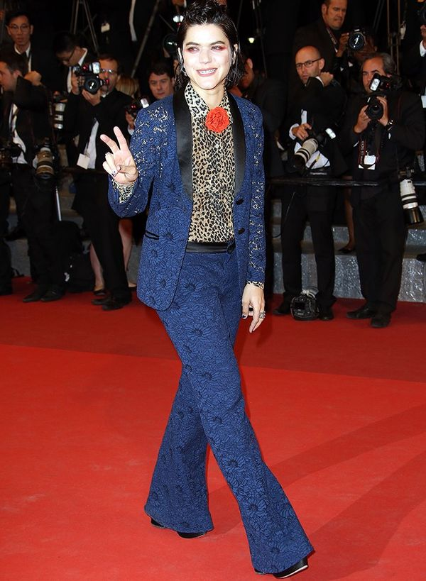 Style Notes: Not content with one statement, SoKo breezes through three. Her Gucci trouser suit looks brilliant and bold with a leopard shirt and red corsage.
