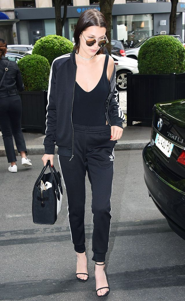 On Bella Hadid: Quay sunglasses; Céline tote; Adidas Supergirl Track Jacket ($70) and Supergirl Trackpant ($60); Are You Am I Naia Bodysuit ($129); Stuart Weitzman Nudist Sandals ($398).