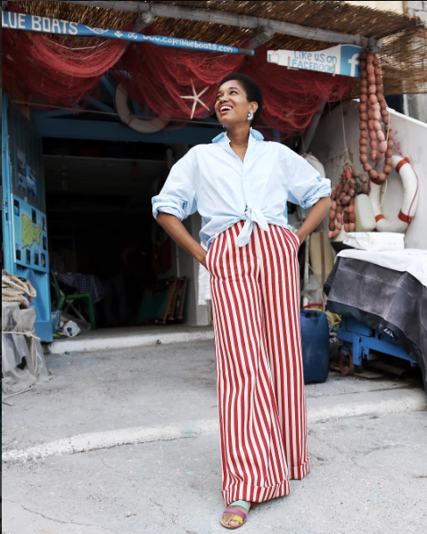 Style Notes: Tamu kept things classic here by pairing those wide-leg trousers with a simple blue button-down shirt. The key is all in the styling—roll up those sleeves, and be sure to tie...