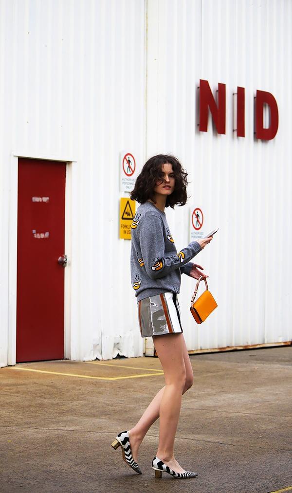 On Chloe Hill: Acne Studios Dasher Hot Dog ($380); Prada skirt; Oroton Estate Crossbody Bag ($215); Nicholas Kirkwood Briona Prism Pumps ($201).