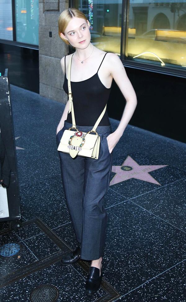 elle fanning wearing bodysuit trousers and miu miu bag