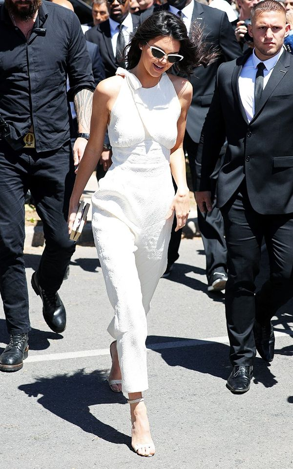 Kendall Jenner wearing white jumpsuit and cat-eye sunglasses