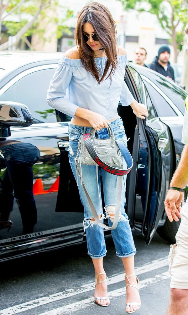 Kendall Jenner wearing off the shoulder top, jeans and heeled sandals
