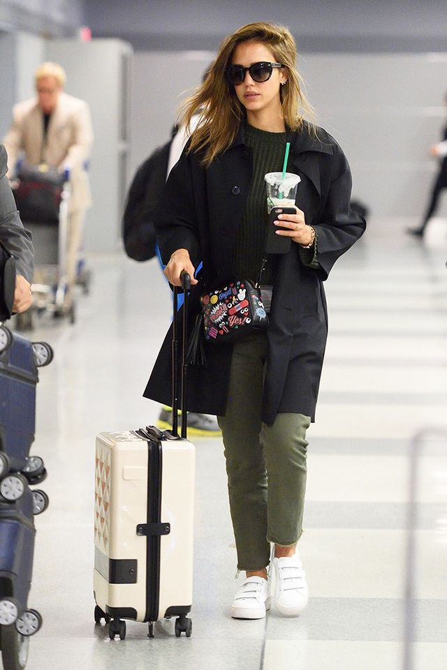 On Jessica Alba: Etro sunglasses; The Great Slouch Army Pants ($171); Anya Hindmarch All Over Wink Crossbody Bag ($1295); Loms Carry-On Spinner ($695); Sandro sneakers.
