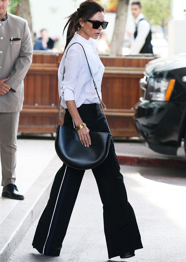 Style Notes: Following her turn on the Cannes red carpet, VB took up the airport dressing baton and hit the other kind of runway in wide-leg trousers, shirting, black-out shades and...