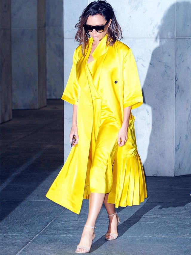 Style Notes: In a Victoria Beckham yellow satin coat and matching dress, the designer made a decisive move away from her signature black—and we, her adoring audience, lapped it up.