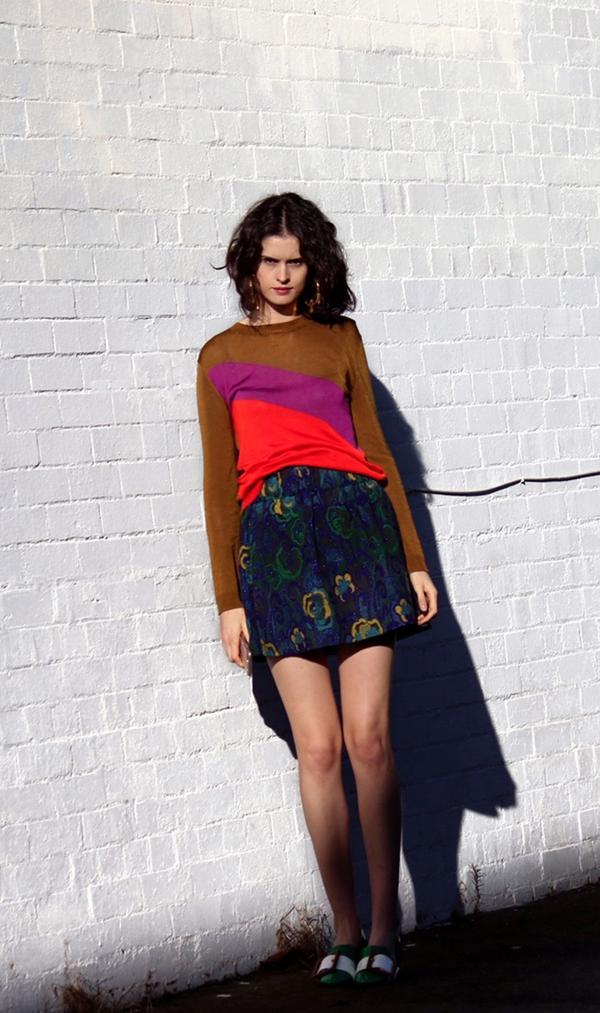 On Chloe Hill: Karen Walker Correspondent Sweater($205); Karen Walker skirt; Miu Miu Buckled Patent-Leather Pumps($1100); Christie Nicolaides Phoenix Hoops Gold($219).