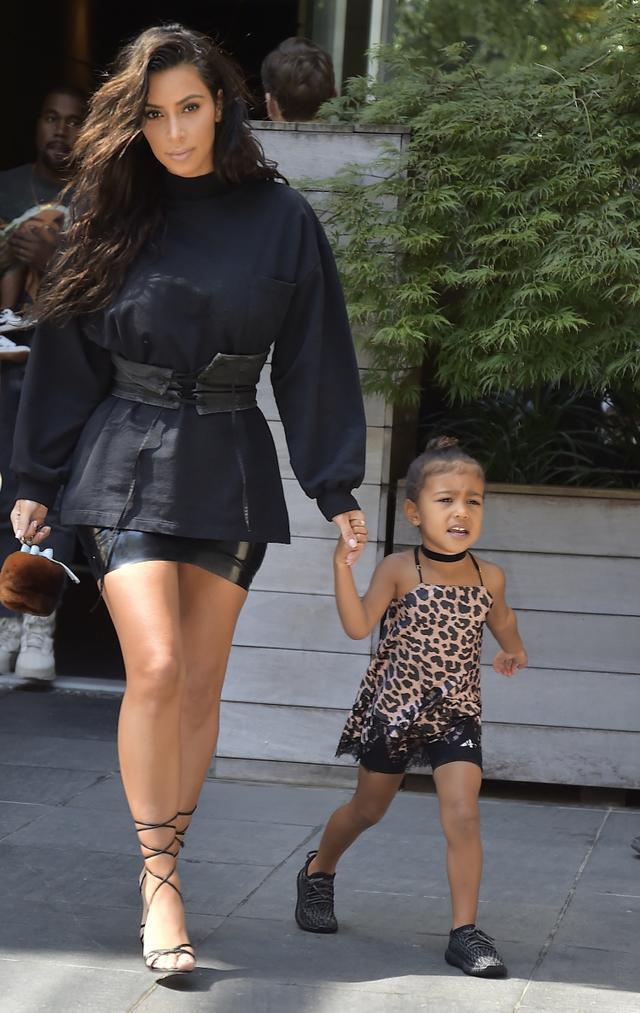 On North West: Yeezy Boosts 350 sneakers. On Kim Kardashian West: Atsuko Kudo mini skirt; Manolo Blahnik Leva sandals.
