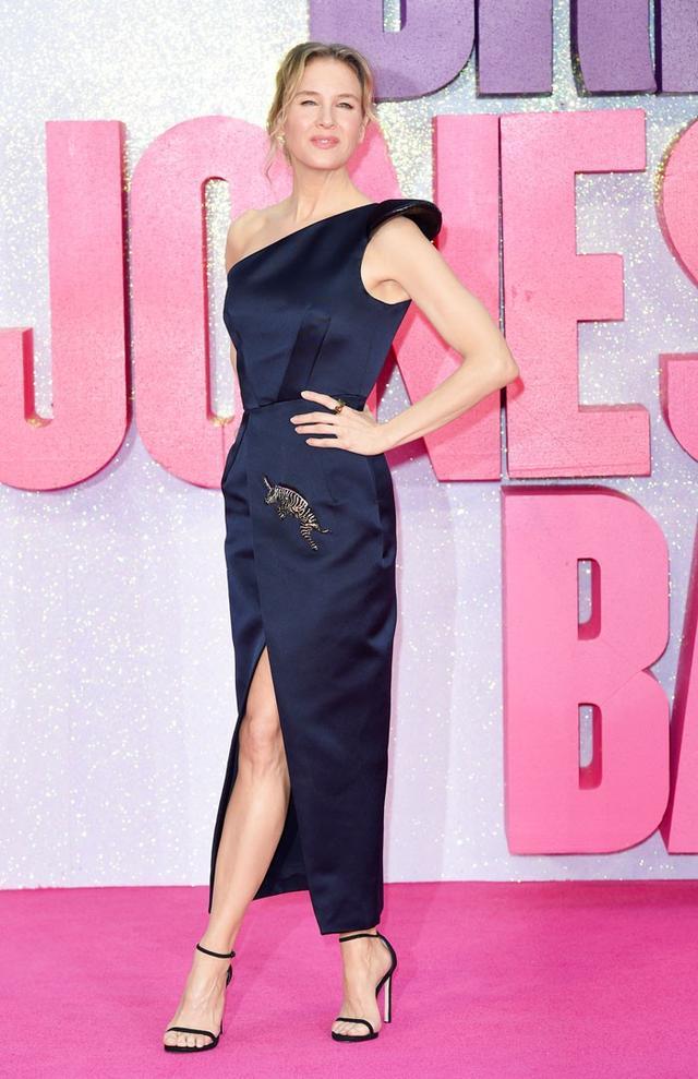 On Renée Zellweger:Schiaparelli Haute Couture dress; Stuart WeitzmanNudist High Heeled Sandals($398).