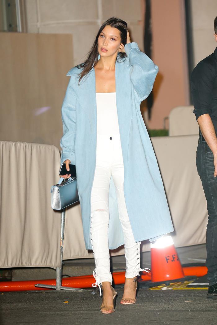 Bella Hadid wearing a denim trench coat and lucite heel yeezy sandals