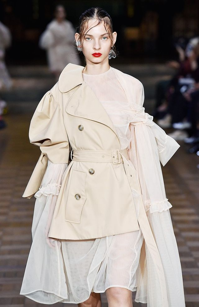 The blown-out proportions of her balloon-sleeved cotton trench or tweed coats were made all the more interesting slung onto one shoulder and through one army only, then fastened in placed with the...
