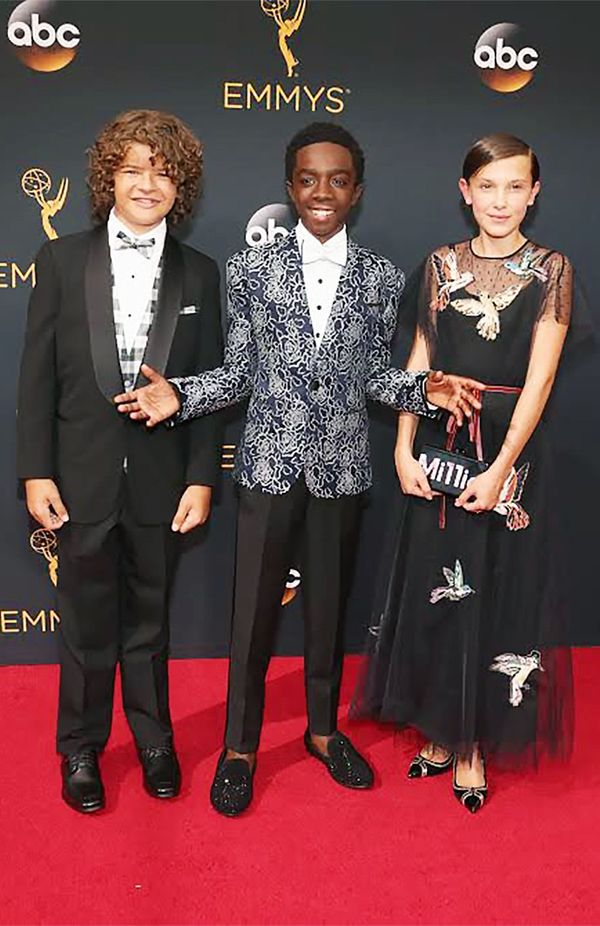 WHO: Gaten Matarazzo, Caleb McLaughlin, and Millie Bobby Brown WHAT: Actors, Stranger Things WEAR: On Millie Bobby Brown: Edie Parker Mi11ie clutch in black; Nicholas Kirkwood Polly Prism Pumps...
