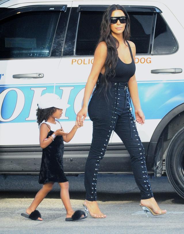 On North West: Akid Troll Aston Slides($40, sold out). On Kim Kardashian West: LPA Bodysuit 23($98).
