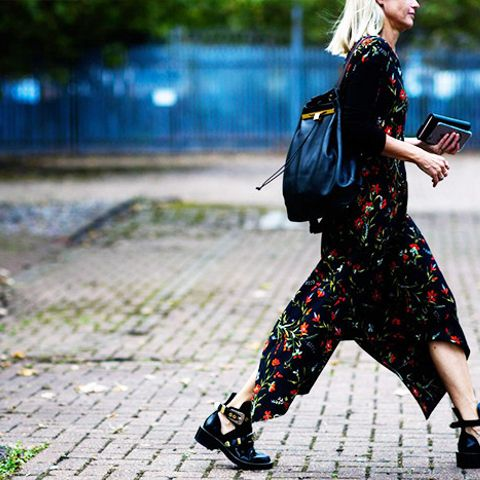 A backpack gives edge to a long floral dress.