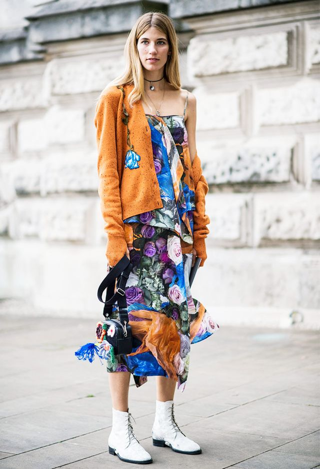 A dress bursting in a bright floral motif is made autumn-ready by way of a matching solid cardigan and lace-up ankle boots.