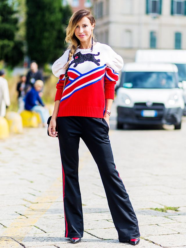 In this look, the sweater's collegiate stripes were echoed in bright red on the sides of oversize pants.