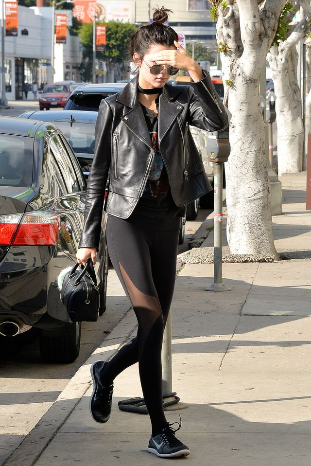 Kendall Jenner wearing black leggings with a black leather jacket, band tee, and sneakers.