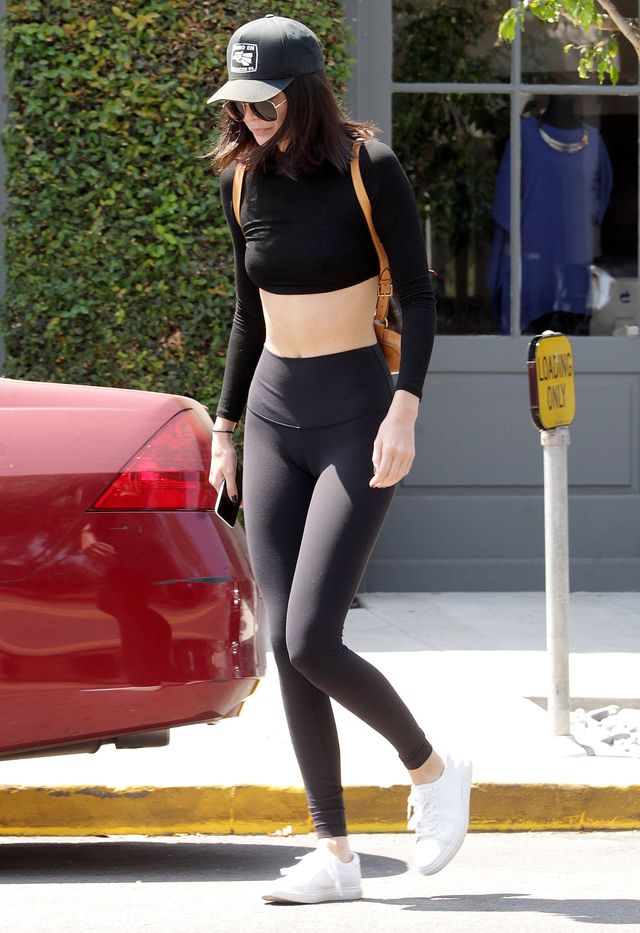 Kendall Jenner wears a black crop top, leggings, and white sneakers.