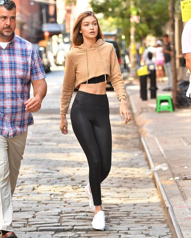 Gigi Hadid wears a brown crop top with black leggings and white sneakers.